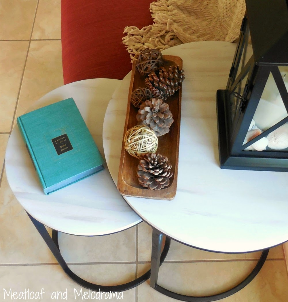 round industrial side tables painted grey and brown with lantern and pinecones