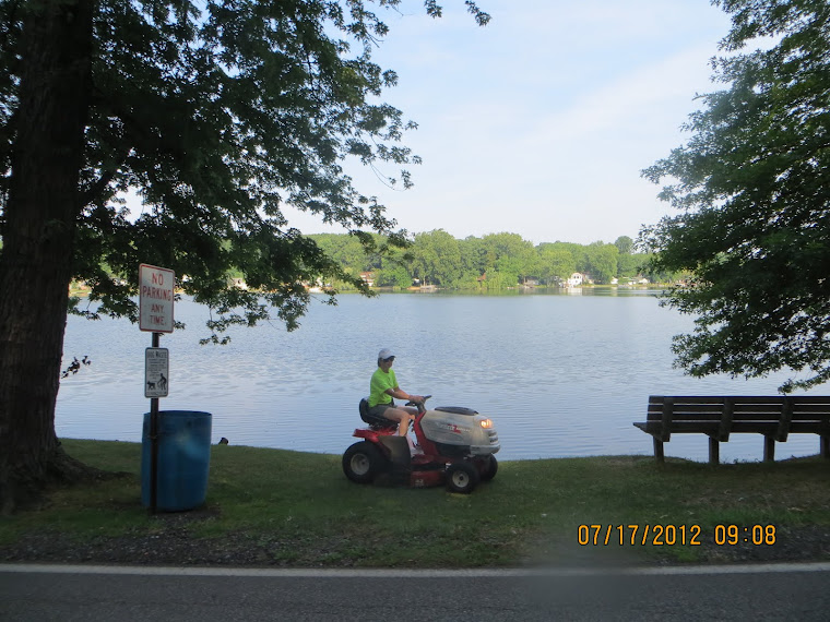 The BLV clerk Honest Ethel's daughter re-mowing short grass by the lake.