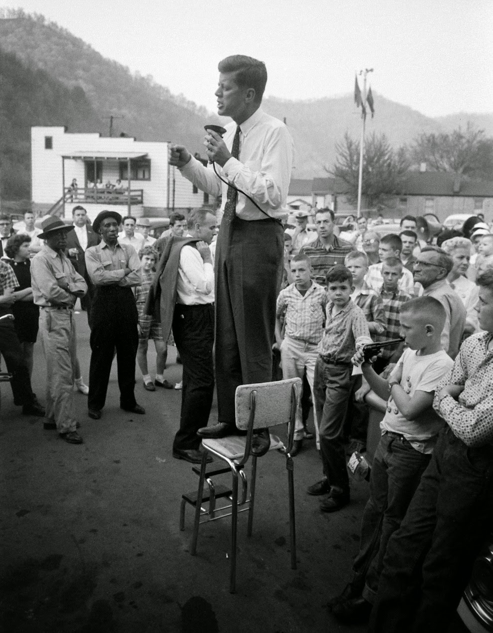 John F. Kennedy campaigns in rural West Virginia looking for support for the May 10th primary, precariously perched on a high-chair to deliver his speech,1960.