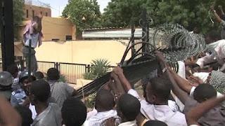 Gente protestanto ante la embajada de alemania en Khartoum.
