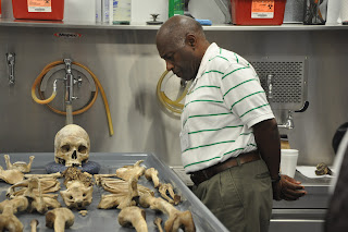 A teacher examines skeletal remains at the Southeast Texas Applied Forensic Science facility.