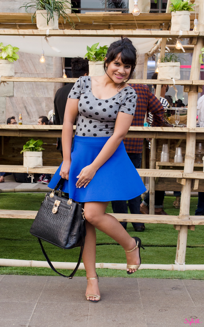 Looking every bit a ballerina, Dayle Pereira of Style pairs her grey polka dot leotard with a blue skater neoprene skirt, gold glitter ankle strap heels, a monogram rose gold satchel bag and a top knot