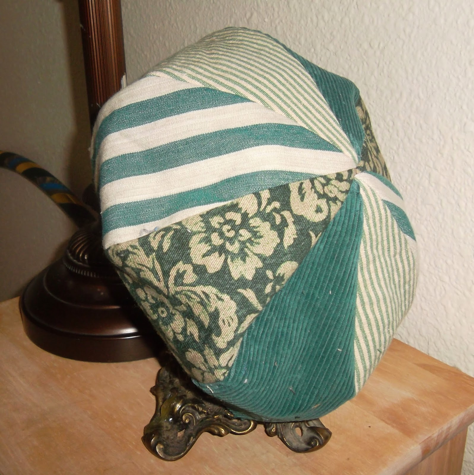Crown of a green, eight-paneled hat, draped over globe-shaped candleholder. The panels alternate between green-on-white floral, thick striped, thin striped and solid green corduroy fabrics.