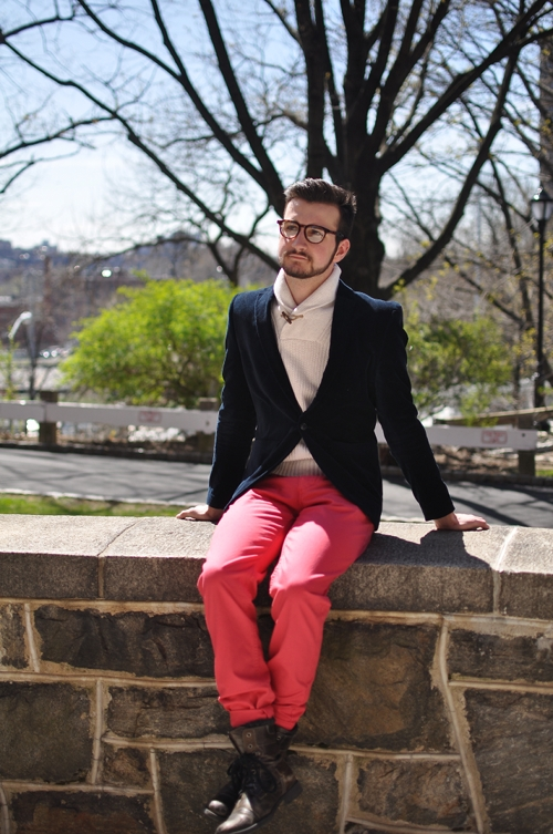 Manhattan college student wearsa navy blazer over a cream white shawl collar toggle closure neck sweater and nantucket red pants rolled up and tucked into a pair of modern brown leather boots.