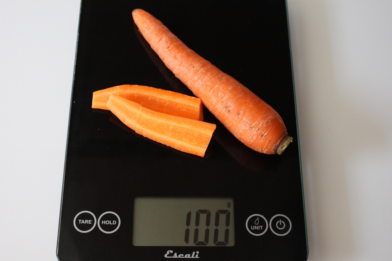 100 grams of carrots, raw, shown on digital scale