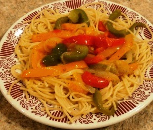 A plate of pasta with peppers and onions
