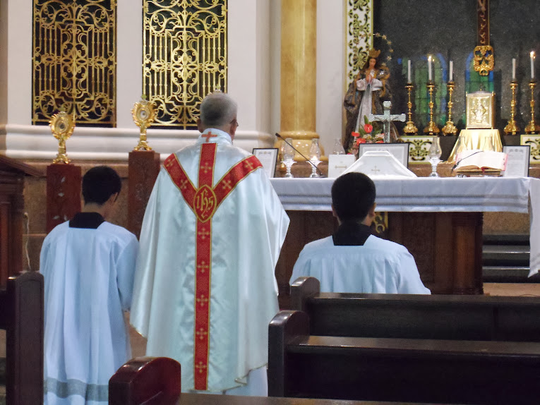 Priest with two servers at the foot of the altar