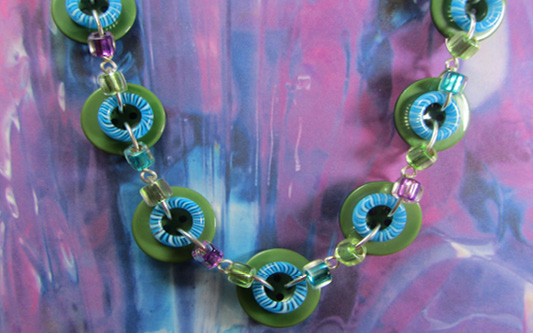 Bold necklace has big green buttons, blue donut beads and small accent beads