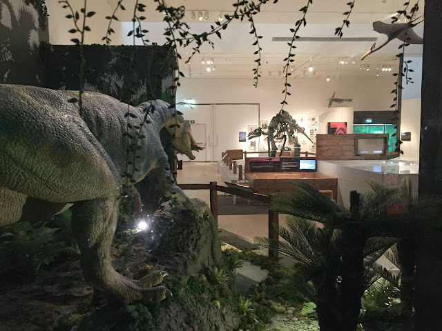 A view of the exhibition including a model dinosaur and skeleton
