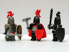 Three Lego knights brandishing a silver sword, a war hammer, and a black sword. The knight on the left wears silver armor; the others are attired in black.