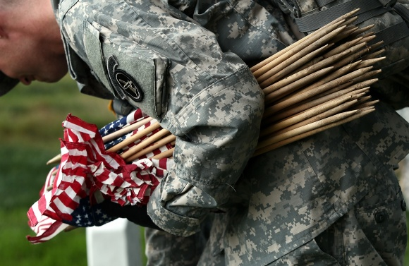 A soldier places flags at Arlington National Cemetery.