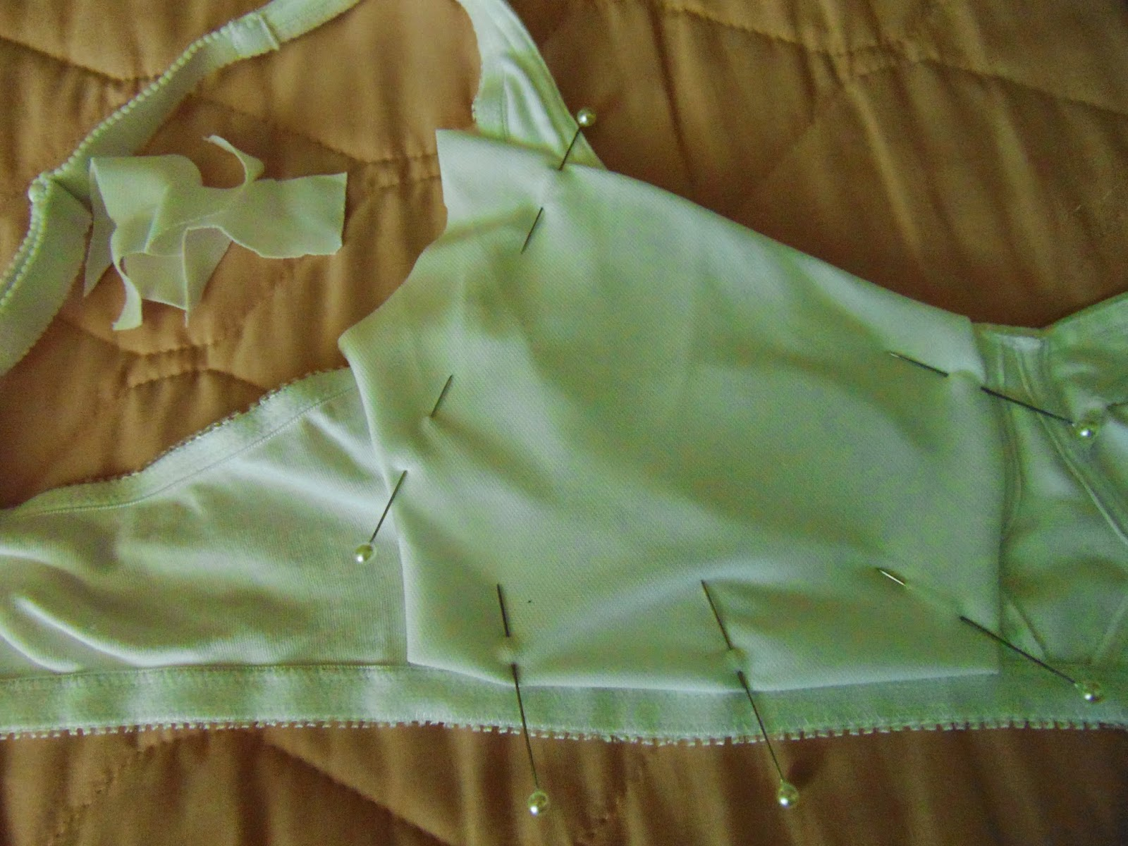 White bra with fabric square edges folded under and pinned in place