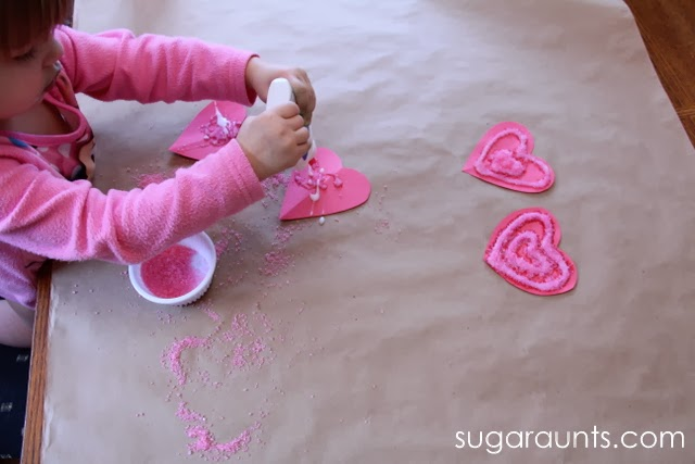 Toddler squeezing glue onto construction paper hearts