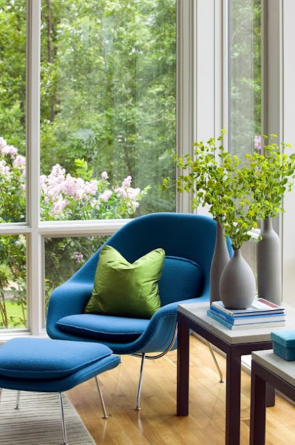 Room with floor to ceiling windows with a garden view, a blue Saarinen womb chair, hard wood floors and two side tables holding bottles of flowers and books