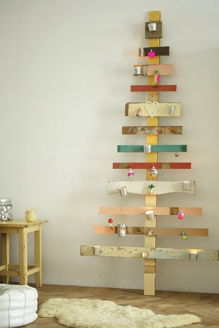 alternative christmas tree with pieces of wood leaning against wall