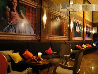 sofá preto, almofadas coloridas, quadros, poltrona Luis XV