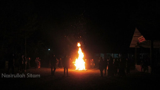 Menghangatkan diri dengan api unggun