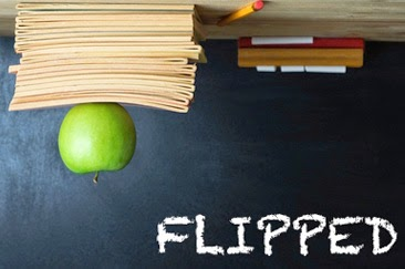 """This is a picture of desk that is upside down and appears to be on the ceiling. On the desk is a stack of book with a green apple on top, along with some chalk and a pencil. The word """"Flipped"""" is in the bottom right hand corner."""
