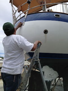 Roberto's assistant buffs the touch-up paint on Whispering Jesse's stern