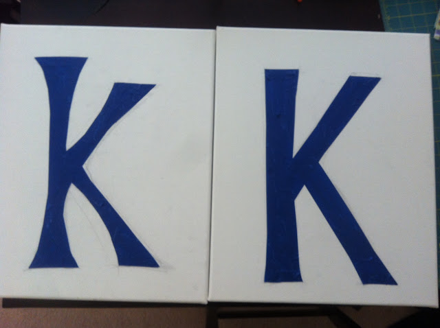"""two white painting canvases with the letter """"K"""" taped off in blue painter's tape"""