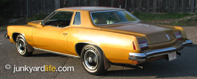 One-year only design of the 1973 Grand Prix featured a distinctive decklid and tail lights. The fuel filler door is beneath the bumper and hard to reach.