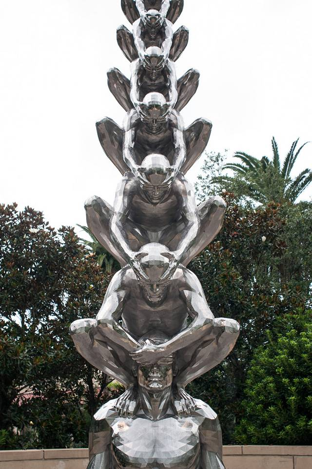 Karma is an intriguing sculptural installation by Korean artist Do Ho Suh that presents countless men sitting atop one another while shielding each other's eyes. Like his Cause & Effect piece, which features a spectacular tornado of figurines, Karma presents figurative sculptures ascending into the sky like a human ladder.