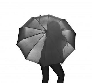 una mujer vista en silueta a través de un paraguas