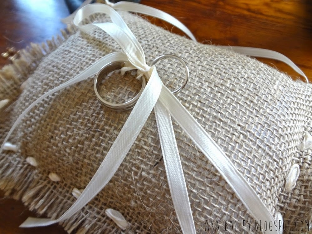 Wedding rings tied with a ribbon onto a burlap pillow