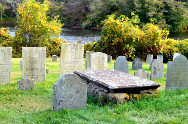 Head stones in cemetary with pond view