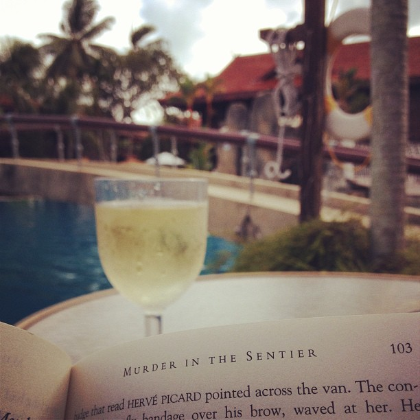 wine and a book by the pool at meritus pelangi resort, langkawi malaysia