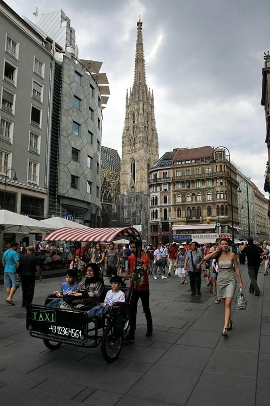 Rua pedonal movimentada, junto à Catedral de Viena. A torre é visível estre os prédios. Em primeiro plano um triciclo com condutor e passageiros