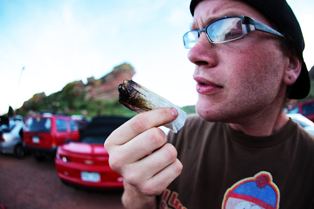 A guy smoking a huge joint outside the BASSNECTAR show at Red Rocks amphitheater.