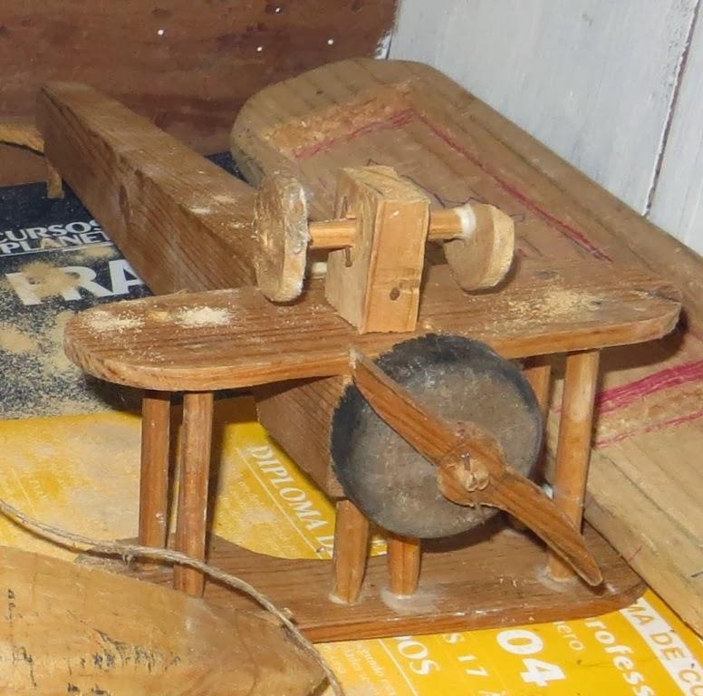 Ampliação de Fotografia macro de Brinquedos Artesanais de Madeira: barco, avião, carroça e cama, com pormenor da hélice