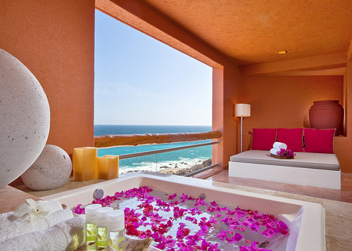 bathroom tub filled with fushia flower petals hotel tub