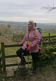 Walker by stile above Blockley in the Cotswolds