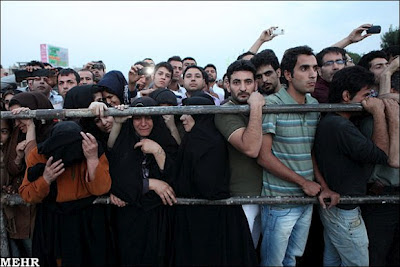 Bystanders watch a public hanging in Iran. Some take pictures with their phones.
