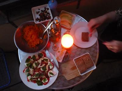 Melone, Tomaten mit Mozarella, Brot, Salat, Nüsse. Käse auf dem Beistelltisch
