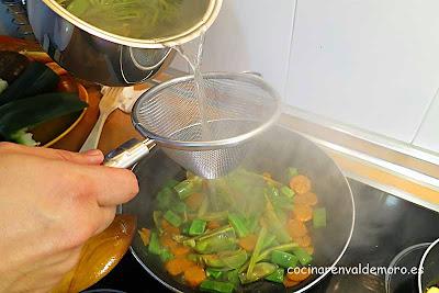 Echando el caldo en la sartén con las verduras