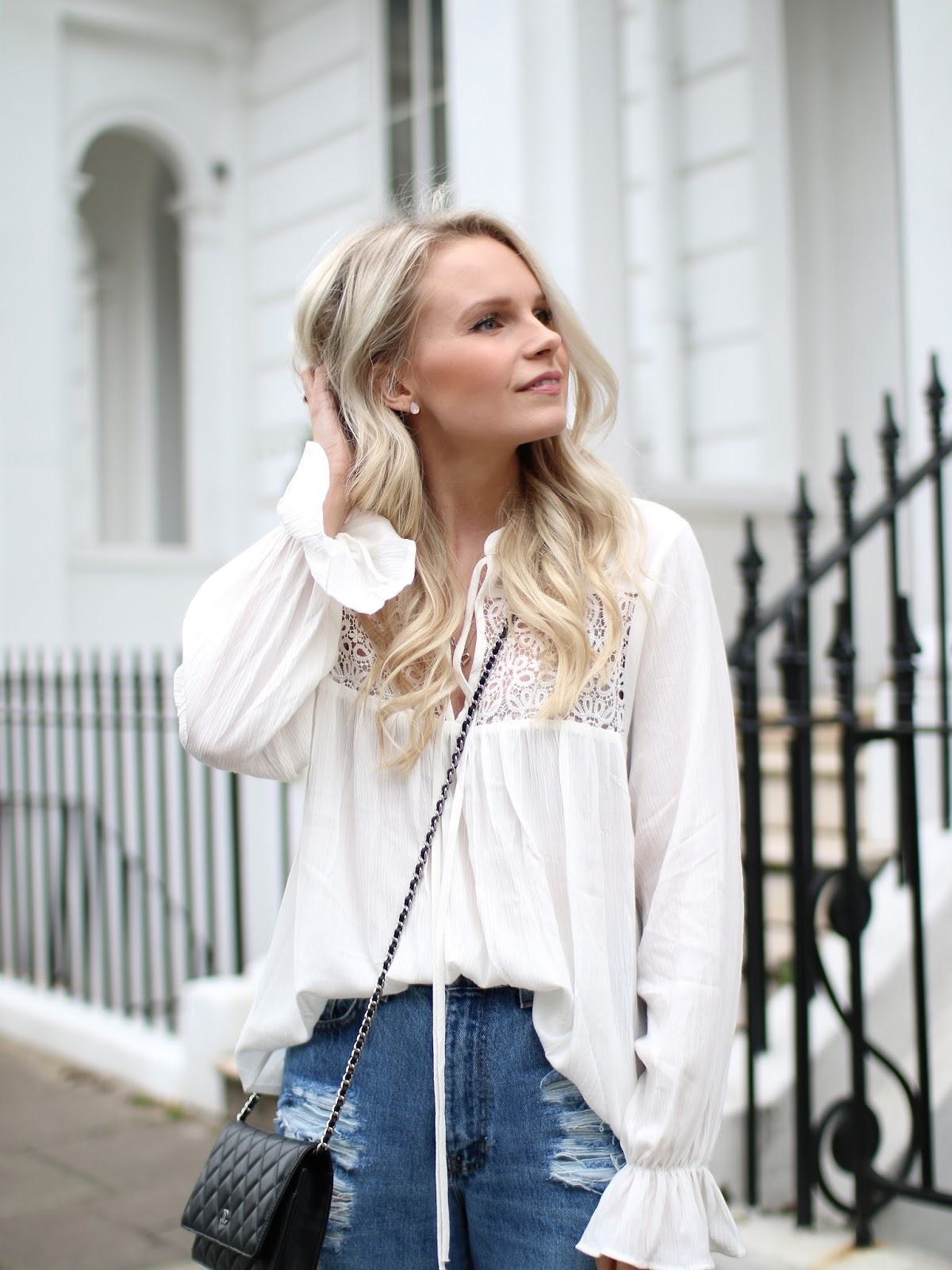 neutral makeup on a blonde women wearing a pretty white lace boho top in H&M and ripped blue jeans
