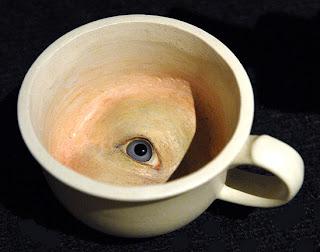 Observado por uma chavena com um olho no interior