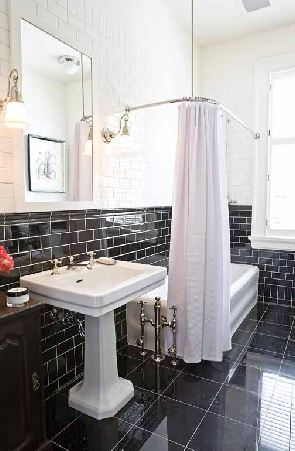 mcintyre bills' black white bathroom bath with black tiles on the floor, black and white subway tiles on the walls, a white freestanding tub with white shower curtain and a white pedestal sink