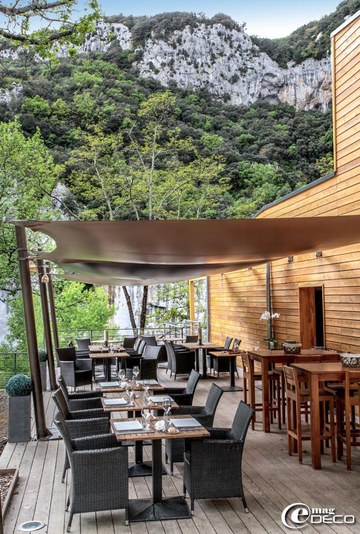 Sous des toiles tendues Soltis Ferrari, Lodge du Pont d'Arc a disposé des tables en bois sur piétement métallique Vega, des fauteuils Maisons du Monde, des tables hautes et chaises bar en bois Alinéa