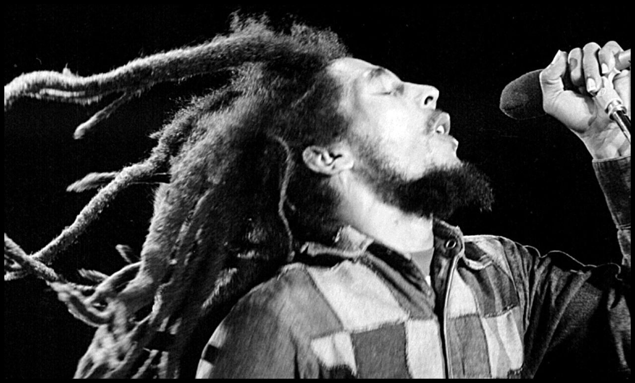 Bob Marley singin with his natural dreadlocks flowing.