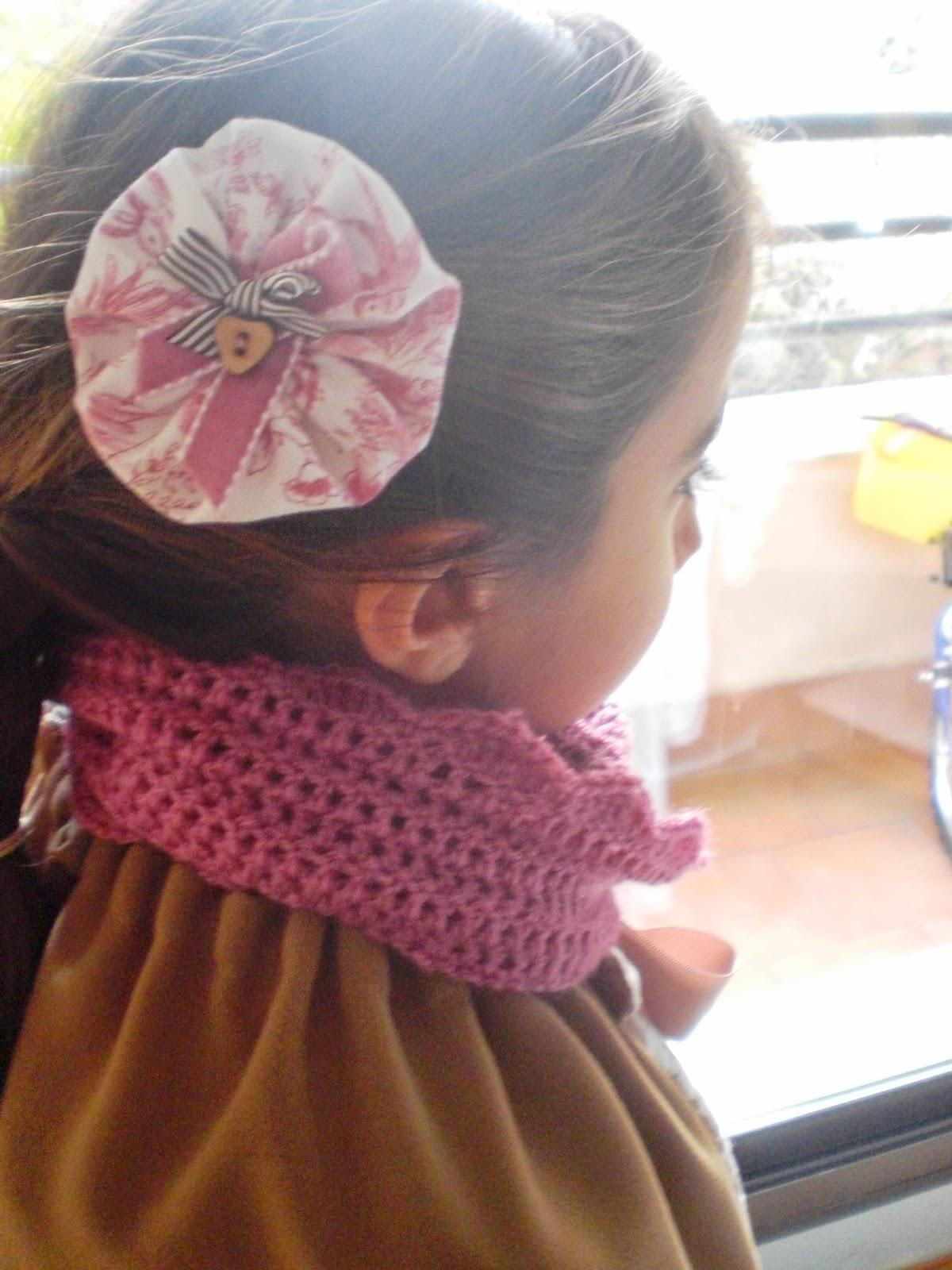 conjunto de bufanda circular (o infinity scarf) para niña, en color rosa palo y puede ir con un adorno para el pelo a juego. Está hecha en crochet.