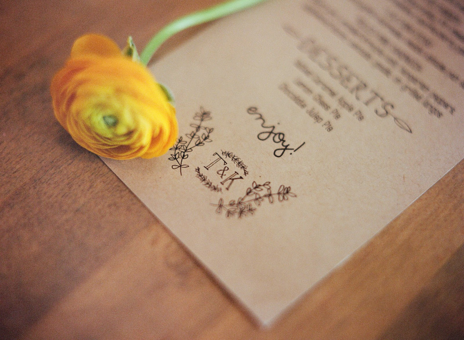 yellow ranunculus flower stem styled with a handmade kraft paper wedding menu for an intimate brooklyn, new york restaurant wedding