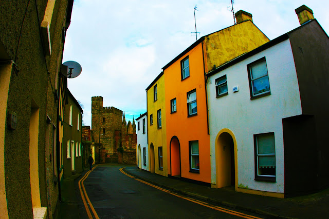 A narrow street past colorful buildings in Wexford, Ireland.