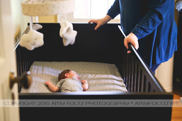 lifestyle photo of newborn in crib