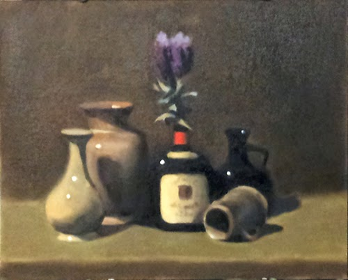 Oil painting of three vases, a black bottle with an off-white label and a red label on its neck with a bunch of plastic lavender protruding from the top, and a stoneware mug resting on its side.