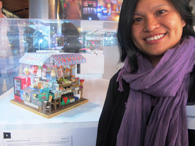 A woman standing next to a miniature model of a traditional Hong Kong Joyful Store.