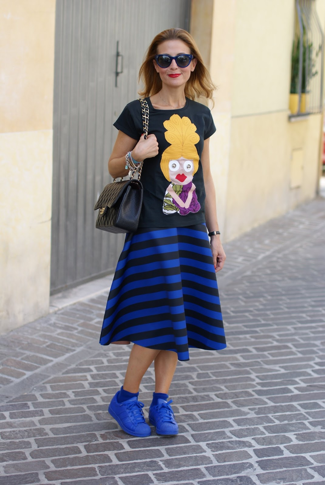 Chanel 2.55 bag and striped midi skirt worn with adidas supercolor blue sneakers on Fashion and Cookies fashion blog, fashion blogger style